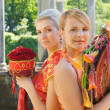 Two beautiful girls with luxury bouquets — Stock Photo