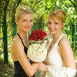 Twe girls with a flowers in green alley — Stock Photo
