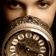 Stock Photo: Sepia picture of a girl's face with a clock (focus on clock)