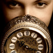 Sepia picture of a girl's face with a clock (focus on clock) — Stock Photo