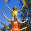 Small girl sitting on a sister's shoulders holding rainbow in — Stock Photo