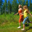 Two girls running on a meadow — Stock Photo #5098134