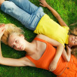 Stock Photo: Two beautiful girls lying on grass