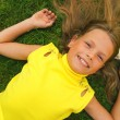 Little girl lying on a green grass — Stock Photo #5098150