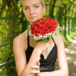 Beautiful blond girl in evening dress holding bouquet of red ros — Stock Photo