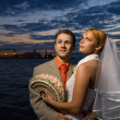 Stock Photo: Bride and groom standing together near the river at the sunset t
