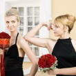 Two beautiful girls with flowers in black evening dresses — Stock Photo
