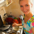 Pretty young girl cooks dinner in the kitchen — Stock Photo