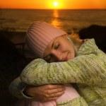 Beautiful girl sleeping on a beach at sunset time — Stock Photo