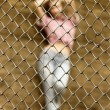 Sexy prisoner behind metal fence — Stock Photo