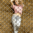 Sexy prisoner behind metal fence - Stock Photo