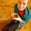Funny blond girl with a cup of coffee sitting on sofa — Foto Stock