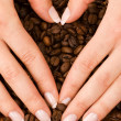 Heart shape with hands above coffee beans — Stock Photo #5098513