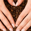 Heart shape with hands above coffee beans — Stock Photo