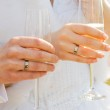 Two hands with wedding rings holding champagne glasses — Stock Photo
