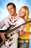 Young musician plays guitar and beautiful blond girl stands near — Stock Photo