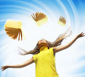 Young happy girl over abstract background and flying books aroun — Stock Photo