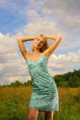 Beautiful girl on the field and blue cloudy sky behind her — Stok fotoğraf