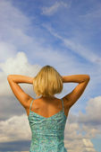 Blond girl from behind blue cloudy sky as background — Stock Photo