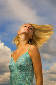 Beautiful blond girl and blue cloudy sky behind her — Stok fotoğraf