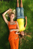 Two girls lying on a green grass — Stock Photo