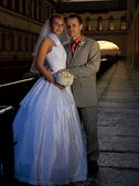 Bride and groom near the river at sunset time — Stockfoto