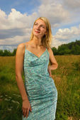 Beautiful blond girl in the field, blue cloudy sky behind her — Stock Photo