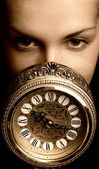 Sepia picture of a girl's face with a clock (focus on clock) — Стоковое фото