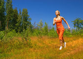 Beautiful girl running in the forest — Stock Photo