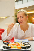 Beautiful girl eats sushi in a restaurant — Stock Photo
