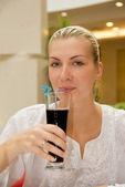 Blond tjej dricka druvsaft i en restaurang — Stockfoto
