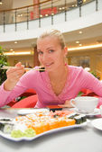 Girl eating sushin in a restaurant — Stockfoto