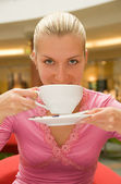 Attractive blond girl drinking coffee in a restaurant — Stock Photo