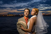 Bride and groom standing together near the river at the sunset t — Stock Photo