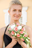 Beautiful blond girl with a bouquet of roses — Stock Photo