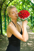 Beautiful blond girl scenting bouquet of red roses — Stock Photo
