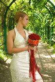 Niña con un ramo de rosas en callejón verde — Foto de Stock