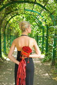 Beautiful blond girl in black evening dress with a bouquet of re — Stock Photo