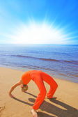 Blond girl shows some yoga moves on the beach — Stock Photo