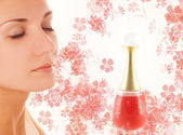Beautiful girl's face and small perfume phial on abstract backgr — Stock Photo
