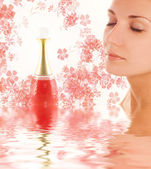 Beautiful girl's face and perfume phial in rendered water — Stock Photo