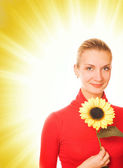 Beautiful girl with a sunflower on abstract background — Stock Photo