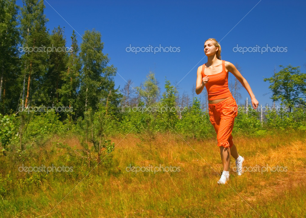 beautiful girl running in the forest stock photo