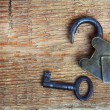 Old padlock and key on wood — Stock Photo