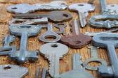Oude sleutels op houten bord — Stockfoto