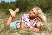 Pretty girl lying on sandy beach — Stock Photo