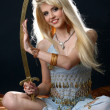 Beautiful sexy blonde in blue east dress with a sword — Stock Photo #3909105