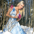 Woman with orchid in the winter forest — Stock Photo