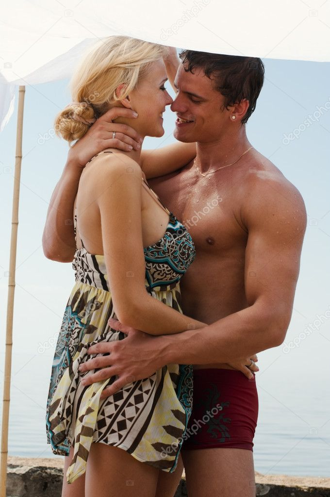 Young beautiful couple are kissing on the beach — Stock Photo #3676325