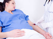 Doctor takes blood at the pregnant woman — Stock Photo